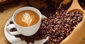 Xicara de cafe ao lado de graos
